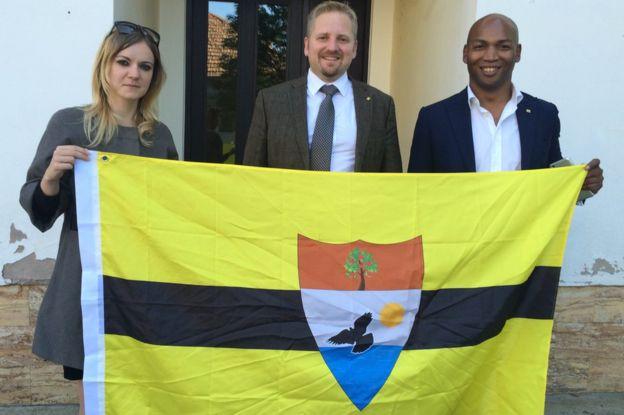 Vit Jedlicka (al centro) con la bandera de Liberland junto a Jose Miguel Maschietto (a la derecha) y su abogada.